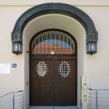 Eingangsbereich mit sanierter historischer Holztür und bogenförmigem Schmuckelement inkl. Außenleuchten aus Kupfer © 2017 Betrieb für Bau und Liegenschaften Mecklenburg-Vorpommern
