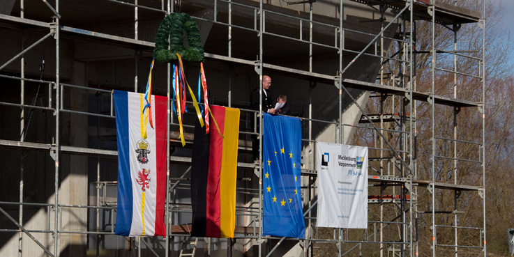 Zimmermann Sven Kitzmann steht auf dem Gerüst und verliest den Richtspruch  © 2018 Betrieb für Bau und Liegenschaften Mecklenburg-Vorpommern