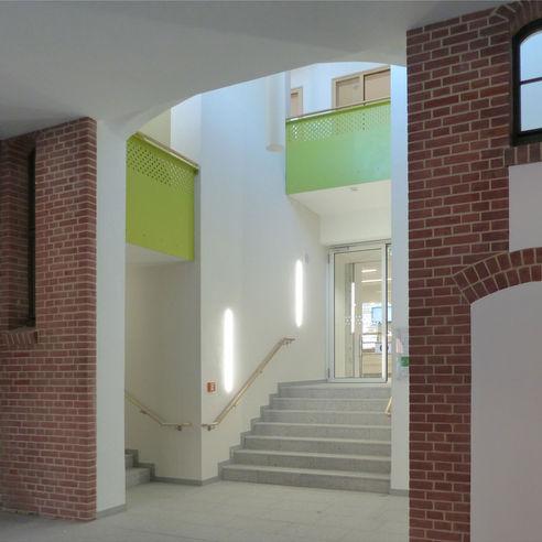 Eingangsbereich Mensa: auch hier sind in den hellen Räumen grüne Farbakzente der Treppen und historisches Backsteinmauerwerk wiederzufinden © 2018 Betrieb für Bau und Liegenschaften Mecklenburg-Vorpommern