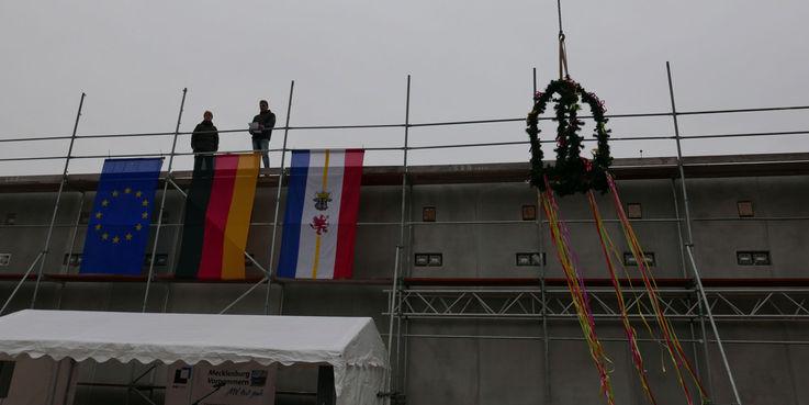 Während der Richtspruch verlesen wird  schwebt die Richtkrone nach oben. © 2018 Betrieb für Bau und Liegenschaften Mecklenburg-Vorpommern