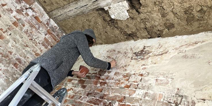 Die Wandmalerei im Haus 12 ist eine kleine Sensation und wird hier im Auftrag des BBL M-V von Restauratorin Karolin Wiench gesichert. © 2019 Betrieb für Bau und Liegenschaften Mecklenburg-Vorpommern