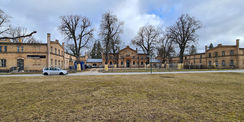 Hofansicht des Marstalls mit Nordflügel (links)  Mittelteil und dem Südflügel gesichert mit einem Bauzaun für die Arbeiten im 4. Bauabschnitt © 2021 SBL Neubrandenburg