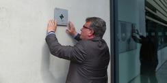 Prof. Dr. Uwe Völker bringt die BNB-Plakette im Eingangsbereich des CFGM gut sichtbar an © 2021 SBL Greifswald
