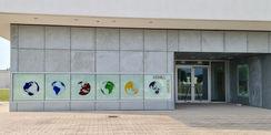 der Haupteingang mit dem im Rahmen der Kunst am Bau vom Künstler Olaf Thaler geschaffenen Hausschild und dem Gebäudewegweiser © 2021 SBL Neubrandenburg