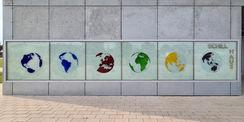 Blick auf das Hausschild mit den sechs Kontinenten – der Künstler Olaf Thaler:  Die sechs globalen Ansichten vermitteln zudem die zentrale  Achse   um die sich die Welt bei aller Vielfalt von Land und Leuten dreht. Das farbige Glas betont die Schönheit  d © 2021 SBL Neubrandenburg